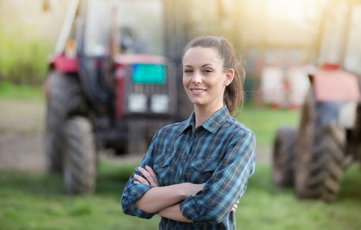 young female farmer standing in front of farm equipment